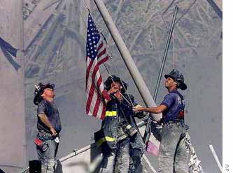 Firefighters raise a US flag