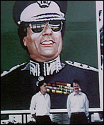 Nick Griffin and colleague stand under a poster of Colonel Gadaffi in Tripoli