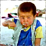 A child feeds himself porridge in Beshkent, Tajikistan
