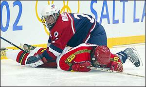 Tara Mounsey of the US gets to her feet after body-checking Linuo Wang of China during the preliminary ice hockey match