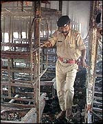 Indian police officer inside a gutted train carriage