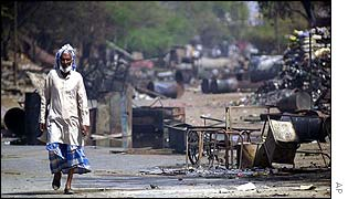 Yukub Qureshi walks through the rubble of an area near Ahmedabad