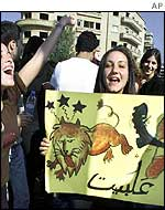 Anti-Syrian protesters with placard showing a Syrian lion (Arabic: al-Assad) being kicked out of Lebanon