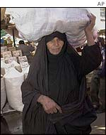 Iraqi woman carries market produce