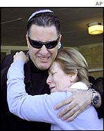 Israeli Knesset Member Naomi Blumental (R) comforts the brother of Gad Rejwan, killed by a Palestinian