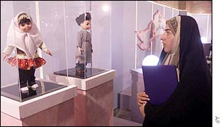 An Iranian woman looks at the Sara (L) and Dara dolls