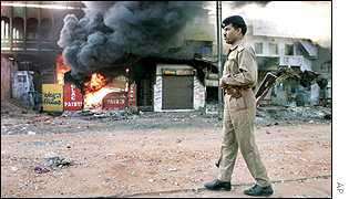 Soldier patrols in front of burning shops