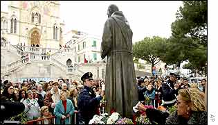 Police and crowds gather round the 'weeping' statue of Padre Pio