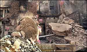 A woman works through the wreckage of a burnt house in Ahmedabad