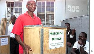 Election official carries a ballot box in Harare