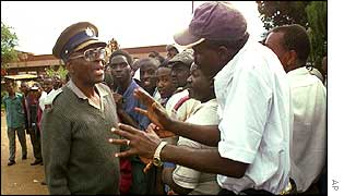 A man who waited hours to vote at the Kuwadzana polling station argues with a police officer
