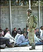Israeli soldier stands guard over Palestinian men rounded up in Tulkarm