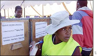 Election observer sits next to ballot boxes