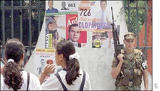 Onlookers walk by a Colombian soldier on patrol surrounded by campaign posters