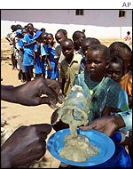 Children queue for food aid in February 2002
