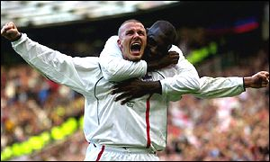 England captain David Beckham is hugged by team-mate Emile Heskey after scoring against Greece in the World Cup qualifier