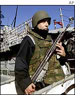 A Spanish soldier stands guard at the warship Vencedora in Barcelona port