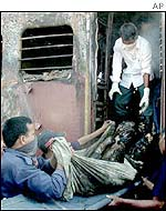 Relief workers remove a body from one of the burned cars of the train set on fire by a mob in Godhra, India