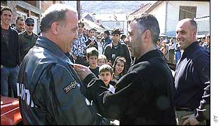 An ethnic Albanian man shakes hands with a member of an ethnically mixed police patrol in Radusa