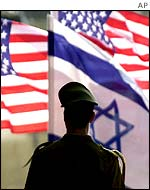 An Israeli soldier looks at American and Israeli flags