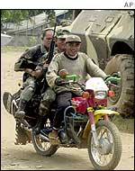 Filipino soldiers ride on motorcycle as they patrol at Isabela town, Basilan island, southern Philippines, 13 March 2002
