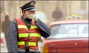 A security guard covers his face with his hand as he stands watch at a street junction in Beijing