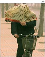 A cyclist tries to cover herself with a scarf