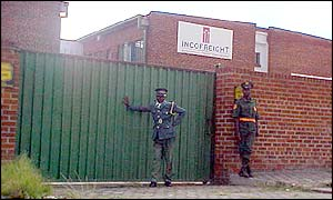 Guards outside a closed factory in Harare