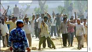 A paramilitary soldier looks at rioters in Ahmedabad