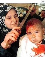 Shia woman cuts the head of a three-year-old boy