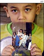 Six-year-old Lawrence William shows the only picture of his mother Ediborah Yap, second from right in picture with fellow nurses, in their house in Lamitan town, Basilan island