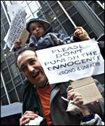 An Andersen employee protests along with his child with a sign saying