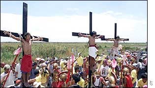 From left, Rolly Turla, Ruben Enaje and Emerito Baking re-enact the crucifixion of Jesus Christ by having themselves nailed on the cross
