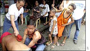An old man hits the back of a flagellant in suburban Mandaluyong City