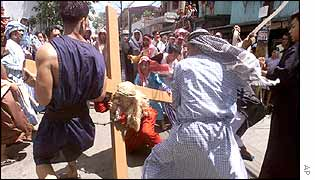 A penitent, dressed as Jesus Christ, is hit by residents of Mandaluyong during a re-enactment of Christ's last days