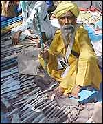 A Sikh vendor sells knives and daggers at the fair