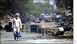 A Muslim man walks past destroyed houses near Ahmedabad