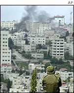 An Israeli soldier looks out over Ramallah as smoke rises over the city