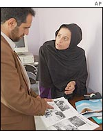 Editor of Afghan women's magazine discusses page layout with colleague