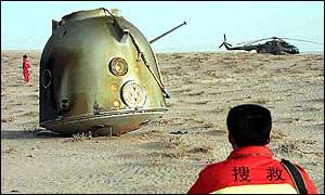 Chinese security personnel surround the unmanned spacecraft Shenzhou III which landed in Inner Mongolia