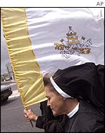 A nun carrying the Vatican flag