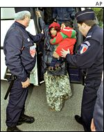 French police escort a refugee woman with a baby from a bus
