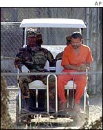 A golf cart is used to move a prisoner in Camp X-Ray
