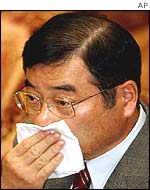Koichi Kato wipes sweat away during his testimony