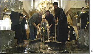Priest and volunteers clean the Church of the Nativity