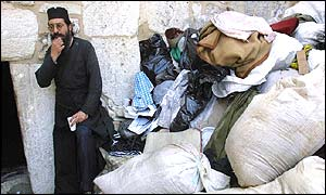 A priest takes a break near a pile of rubbish by the Door of Humility