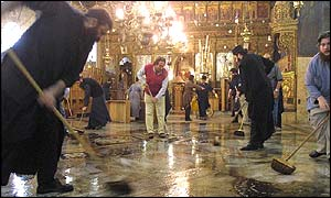 People mopping the floors inside the Church of the Nativity