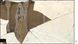 A statue of Mary seen through a broken window