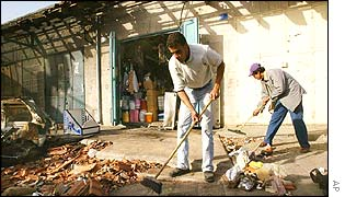 Shop keepers clean a street in Bethlehem