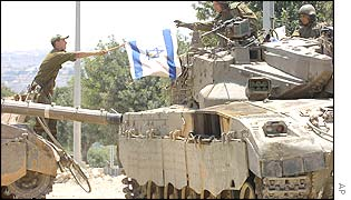 An Israeli soldier passes an Israeli flag from one Merkava tank to another